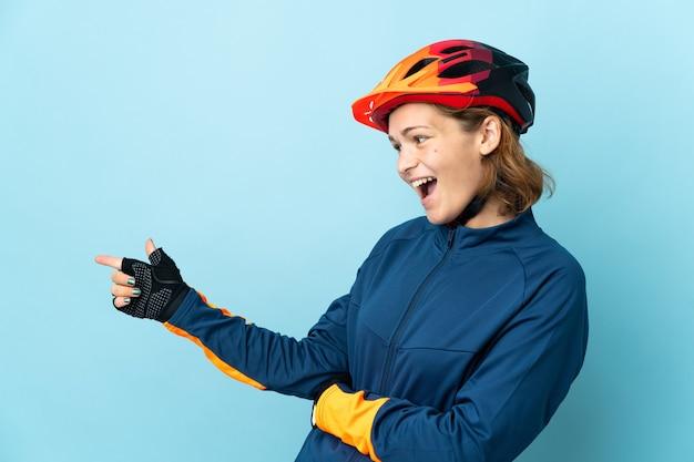 Jonge fietser vrouw geïsoleerd op blauwe achtergrond wijzende vinger naar de zijkant en een product presenteren