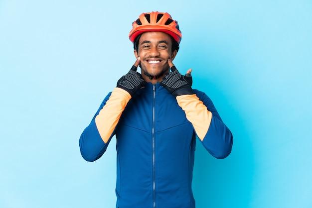 Jonge fietsermens met vlechten over geïsoleerde muur die met een gelukkige en prettige uitdrukking glimlachen