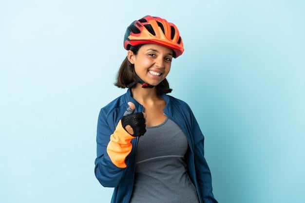 Jonge fietservrouw die op blauwe achtergrond met omhoog duimen wordt geïsoleerd omdat er iets goeds is gebeurd