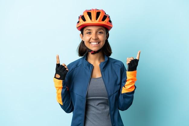 Jonge fietservrouw die op blauwe achtergrond wordt geïsoleerd die een geweldig idee benadrukt