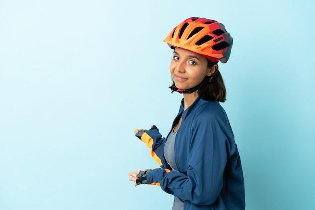 Jonge fietservrouw die op blauwe achtergrond wordt geïsoleerd die handen aan de kant uitbreidt om uit te nodigen om te komen