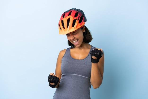 Jonge fietservrouw die op blauwe muur wordt geïsoleerd die een overwinning viert