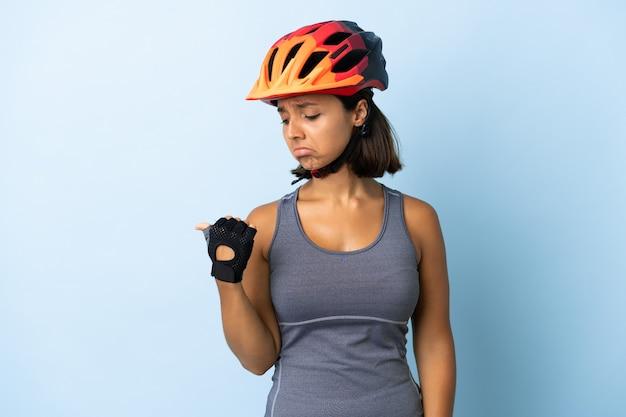 Jonge fietservrouw die op blauwe ongelukkige muur wordt geïsoleerd en naar de kant richt