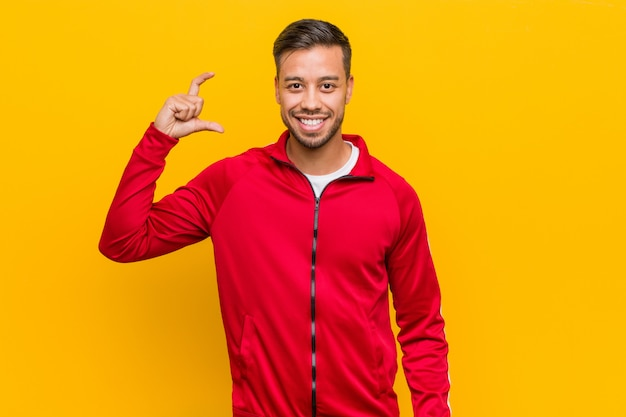 Jonge filipijnse fitness man die iets kleins met wijsvingers, lachend en zelfverzekerd.