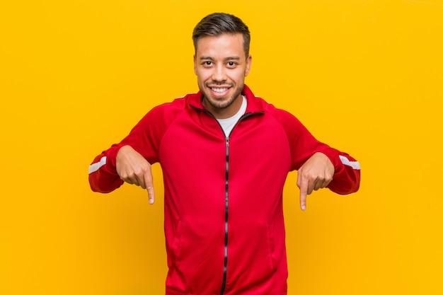 Jonge filipijnse fitness man wijst naar beneden met vingers, positief gevoel.