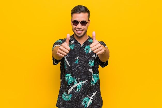 Jonge filipijnse man draagt zomerkleding met thumbs ups, proost over iets, steun en respect concept.