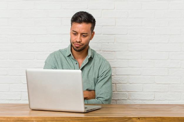 Jonge filipijnse man zit aan het werk met zijn laptop fronsend gezicht in ongenoegen, houdt de armen over elkaar.