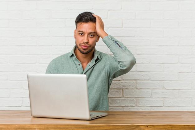 Jonge filipijnse man zit te werken met zijn laptop geschokt, ze heeft belangrijke vergadering onthouden.