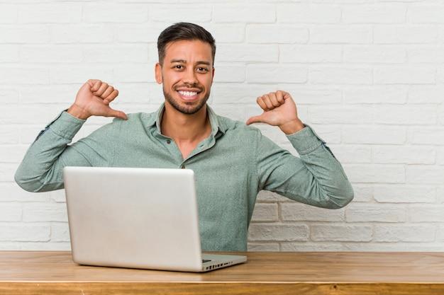 Jonge filipijnse man zit werken met zijn laptop voelt zich trots en zelfverzekerd, voorbeeld te volgen.