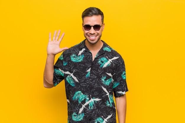 Jonge filipijnse mens die de zomerkleren draagt die vrolijk tonend nummer vijf met vingers glimlacht.