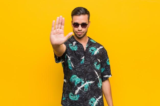 Jonge filipijnse mens die de zomerkleren draagt die zich met uitgestrekte hand bevinden die eindeteken tonen
