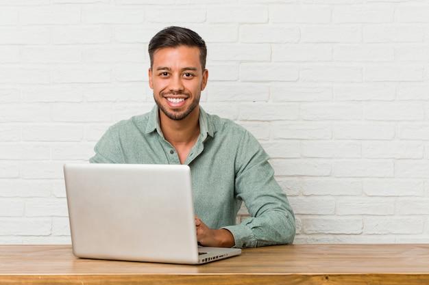 Jonge filipijnse mensenzitting die met zijn gelukkig, glimlachende en vrolijke laptop werken.