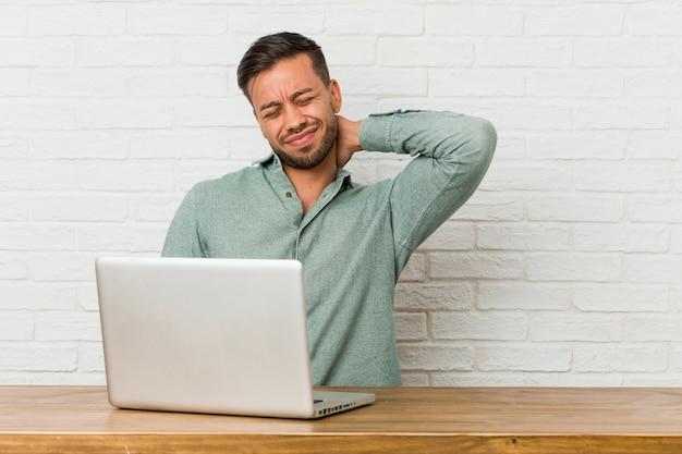 Jonge filipijnse mensenzitting die met zijn laptop werken die aan nekpijn lijden vanwege sedentaire levensstijl.