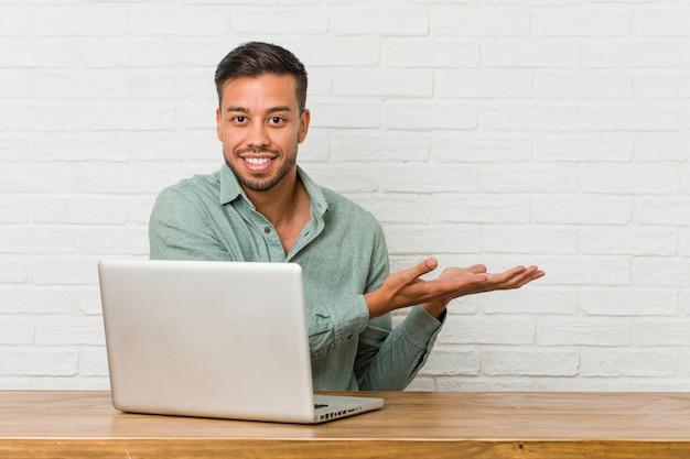 Jonge filipijnse mensenzitting die met zijn laptop werken die een copyon een palm houden.