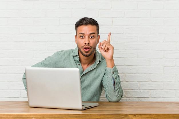 Jonge filipijnse mensenzitting die met zijn laptop werken die een idee hebben