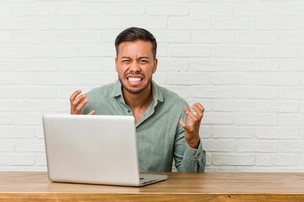 Jonge filipijnse mensenzitting die met zijn laptop werken die met woede gillen.