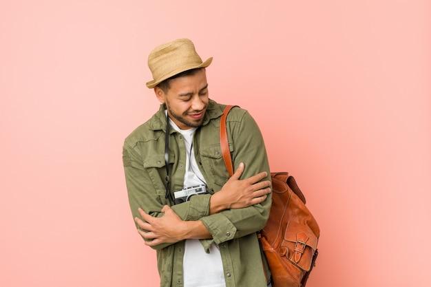 Jonge filipijnse reiziger man knuffels, glimlachend zorgeloos en gelukkig.