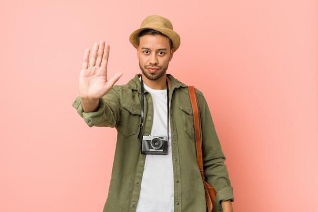 Jonge filipijnse reizigersmens die zich met uitgestrekte hand bevinden die eindeteken tonen