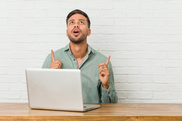 Jonge filippijnse mensenzitting die met zijn laptop werkt die bovenkant met geopende mond richt.