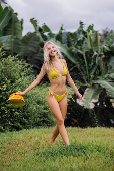 Jonge fit blanke vrouw met blond haar in gele bikini en trendy zomer panama plezier op tropisch veld