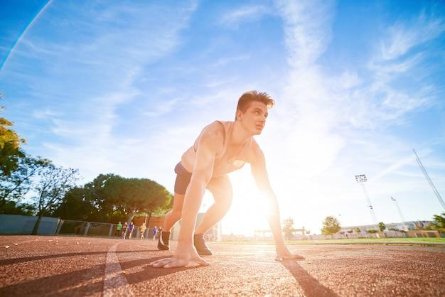 Jonge fit en zelfverzekerde man in startpositie klaar voor hardlopen