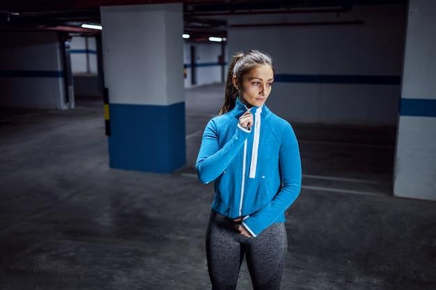 Jonge fit kaukasische sportvrouw in trainingspak die snel in garage loopt.