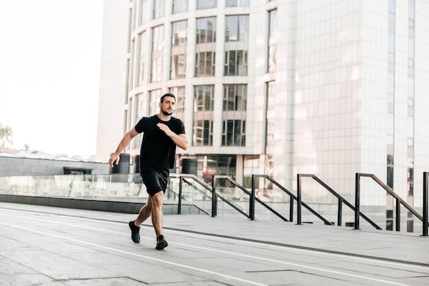 Jonge fit man doet stedelijke hardlooptraining op asfaltweg sprinten in sport en gezonde levensstijl concept. grote stad op de achtergrond. zwarte sportkleding. blanke man joggen.
