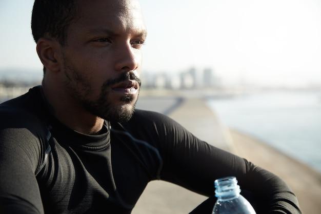 Jonge fit man op het strand drinkwater