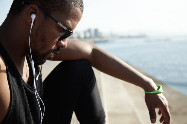 Jonge fit man op het strand met een zonnebril