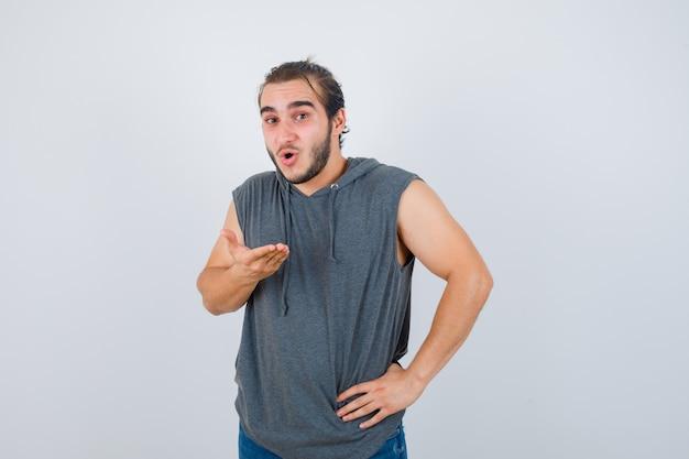 Jonge fit man poseren met de hand op de taille terwijl de handpalm in mouwloos vest wordt verspreid en er geschokt uitziet. vooraanzicht.