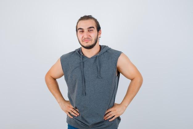 Jonge fit man poseren met de handen op de taille in mouwloze hoodie en op zoek vrolijk. vooraanzicht.