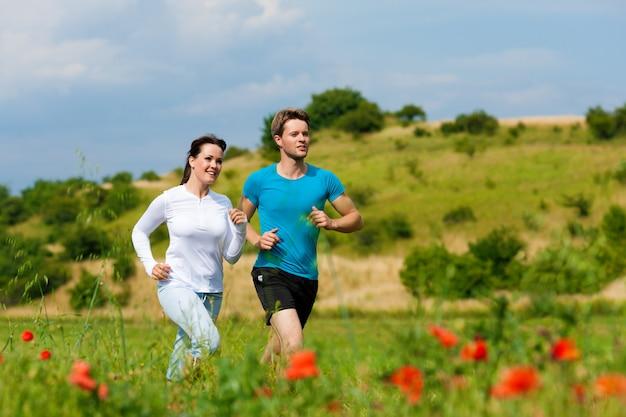 Jonge fit paar joggen in de natuur