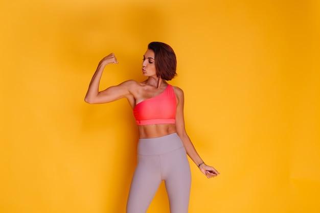 Jonge fit vrij sterke vrouw gekleed in sportkleding, stijlvolle top en legging, poseert tegen gele muur