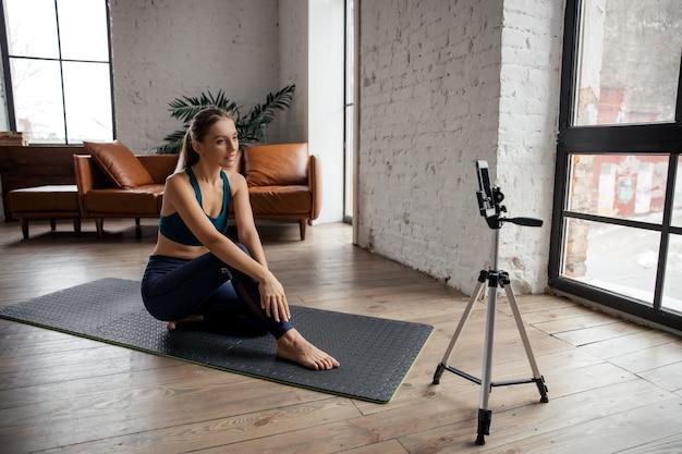 Jonge fit vrouw blogger in sportkleding schiet video op telefoon terwijl ze thuis in de woonkamer oefeningen doet. hoge kwaliteit foto