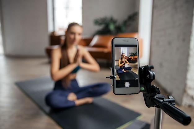 Jonge fit vrouw blogger meditatie en online vertaling opnemen per telefoon. live concept. hoge kwaliteit foto