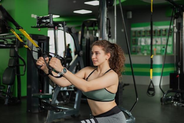 Jonge fit vrouw doen oefening met fitness riemen in de sportschool. functionele training. gezonde levensstijl. fitness en bodybuilding
