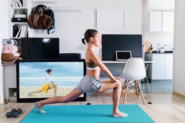 Jonge fit vrouw doet yoga stretching oefening binnen in de buurt van tv-scherm op isolatie bij haar thuis