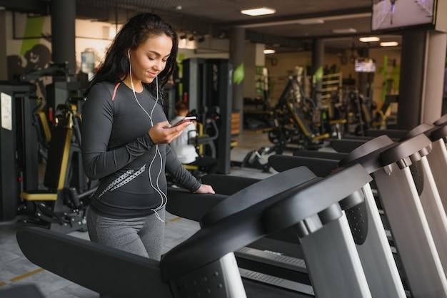 Jonge fit vrouw draait op loopband luisteren naar muziek via hoofdtelefoon op sportschool. concept van een gezonde levensstijl.