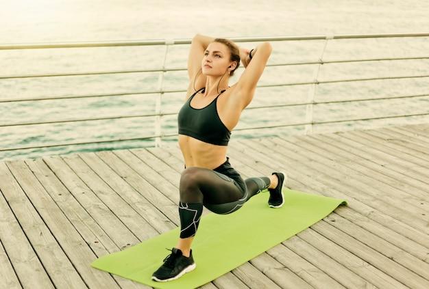 Jonge fit vrouw in sportkleding beoefenen van yoga asana oefeningen op houten terras op het strand aan zee.