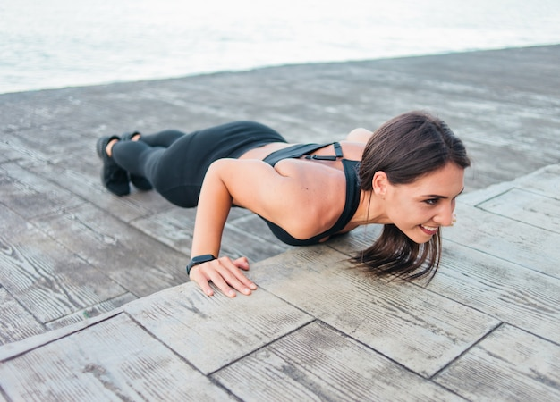 Jonge fit vrouw in sportkleding doet push ups oefenen op het strand
