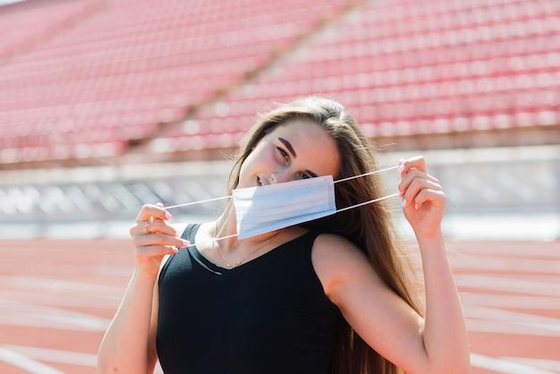 Jonge fit vrouw in sportkleding en beschermend masker voor coronavirus op rode baan en volleybalveld tijdens buitentraining in het stadion