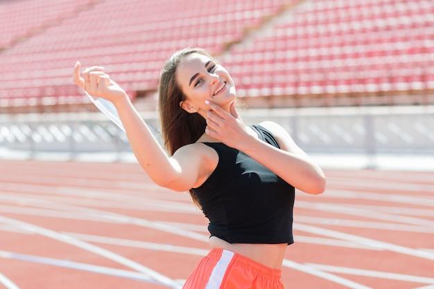 Jonge fit vrouw in sportkleding en beschermend masker voor coronavirus op rode baan en volleybalveld