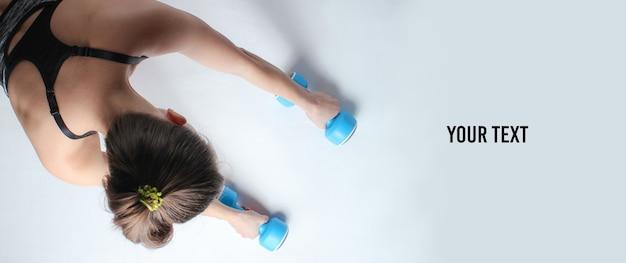 Jonge fit vrouw in sportkleding klaar om push-ups te doen met halters op witte achtergrond. kopieer ruimte. bovenaanzicht