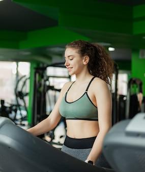 Jonge fit vrouw in sportkleding voordat basistraining draait op een loopband in de sportschool. het concept van een gezonde levensstijl, warming-up, fitness.