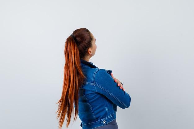 Jonge fit vrouw in top, spijkerjasje knuffelt zichzelf en kijkt peinzend, achteraanzicht.