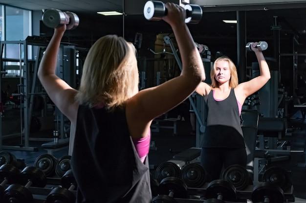 Jonge fit vrouw op de sportschool doet zware oefening met halters. vrouwelijke atleet in een fitnessruimte uit te werken met hand wegen