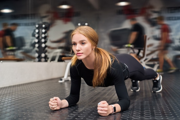 Jonge fit vrouw plank oefening in moderne sportschool doet