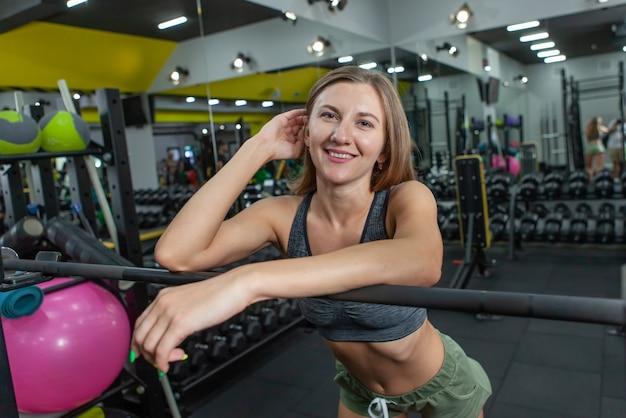 Jonge fit vrouw rusten leunend op een barbell in een moderne sportschool. fitness en bodybuilding