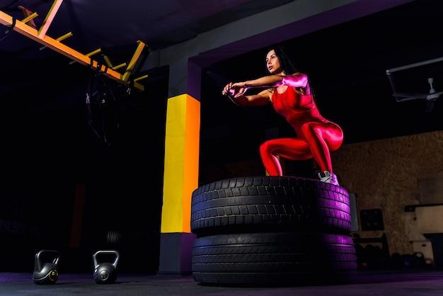 Jonge fit vrouw springen op training wiel op sportschool.