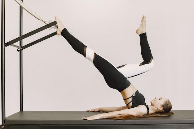 Jonge fit vrouw training in de sportschool. vrouw die zwarte sportkleding draagt. kaukasisch meisje dat zich uitstrekt met apparatuur.